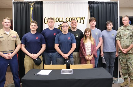 Marine officer and Army officer stand with seven signees from CCHS.