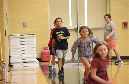 Students running in gym.
