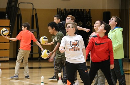 A line of middle school students practice serving in volleyball