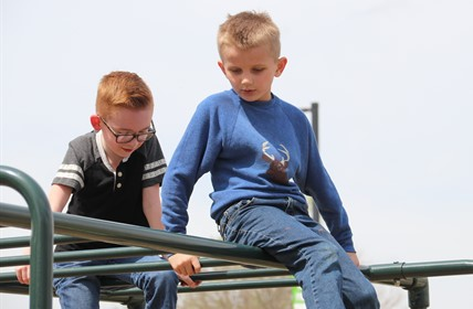Two students sit atop a jungle gym, looking down.